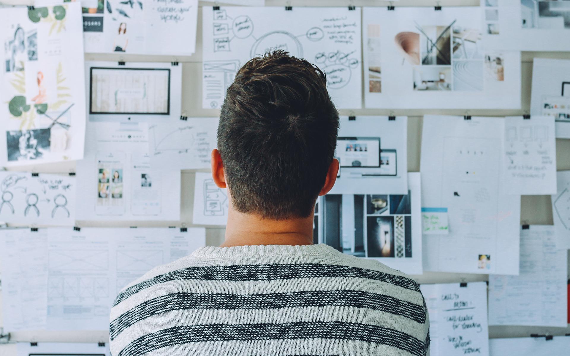En la imagen se ve un hombre de espaldas mirando a una pizarra con muchas notas para planificación.